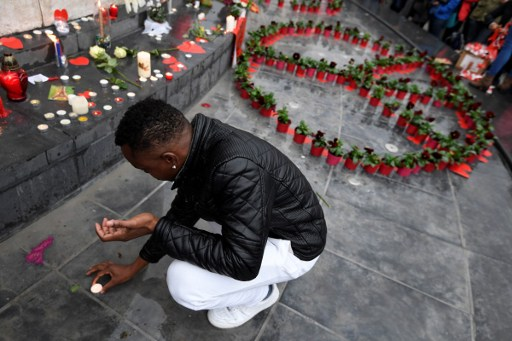 A man puts a candle near a peace symbol made with flowers on place de la Republique in Paris on November 13, 2016 as France marked the first anniversary of the Paris attacks with sombre ceremonies and painful memories for the relatives of the 130 people killed. 130 people were killed on November 13, 2015 by gunmen and suicide bombers from the Islamic State (IS) group in a series of coordinated attacks in and around Paris. / AFP PHOTO / ALAIN JOCARD