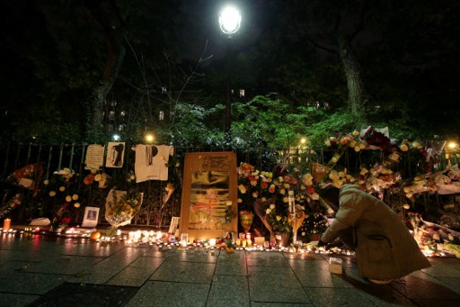 A man lights a candle at a makeshift memorial near the Bataclan concert hall in Paris on November 13, 2016 as France marked the first anniversary of the Paris attacks with sombre ceremonies and painful memories for the relatives of the 130 people killed. 130 people were killed on November 13, 2015 by gunmen and suicide bombers from the Islamic State (IS) group in a series of coordinated attacks in and around Paris. / AFP PHOTO / JOEL SAGET